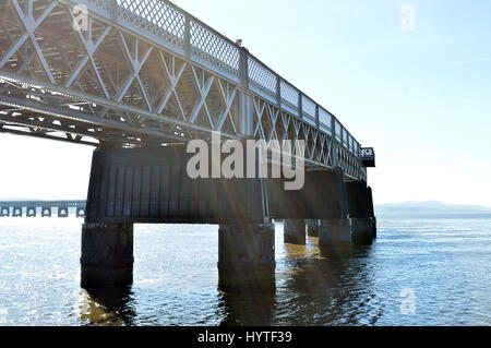 Sun streams through the supports on the Tay Railway Bridge as it crosses the River Tay between Dundee and Wormit - Stock Photo