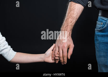 Partial view of father and his little daughter holding hands on black - Stock Photo