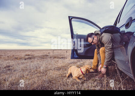 Hiker sitting in the car and preparing their footwear beside him is a small yellow dog - Stock Photo