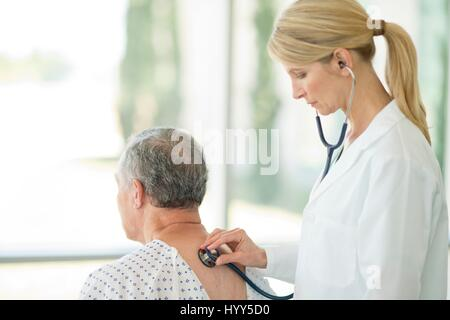 Female doctor using stethoscope on male patient. - Stock Photo