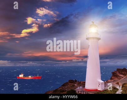 Sunset seascape, lighthouse on the bluff - Stock Photo