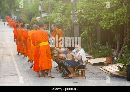 Lao People's Democratic Republic, Luang Prabang - 20 JUNE: People giving alms to buddhist monks on the street, Luang - Stock Photo