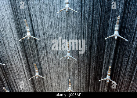silver male sculpture installed to create a jumping effect on the fountain of Dubai Mall in Dubai, United Arab Emirates. - Stock Photo