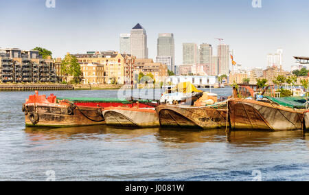 The skyline of London's Docklands financial district rises above old industrial waterhouses and barges on the River - Stock Photo