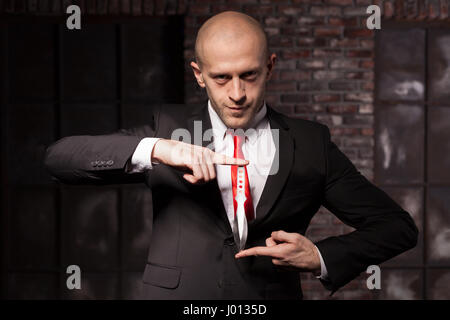 Silent assassin, oriental martial arts in action. Bald contract murderer in suit and red tie holds combat knife. - Stock Photo