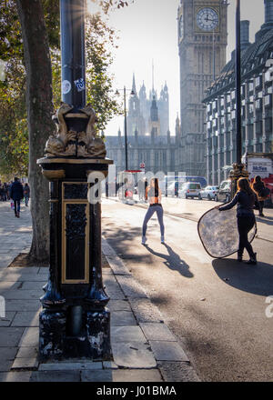 London, England. Model Posing for photographer in a bike lane front of the UK Houses of Parliament, Westminster - Stock Photo
