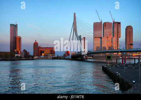 City centre of Rotterdam at sunset in Holland, Netherlands, downtown skyline, skyscrapers and Erasmus Bridge (Erasmusbrug) - Stock Photo