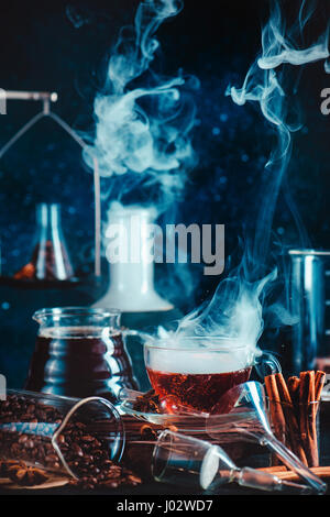 Dark food photo with steaming cup of coffee, cinnamon, laboratory funnel, beakers and test tubes - Stock Photo