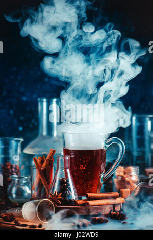 Dark food photo with steaming cup of coffee, spices, anise, and cinnamon, in laboratory setting with funnel, beakers - Stock Photo