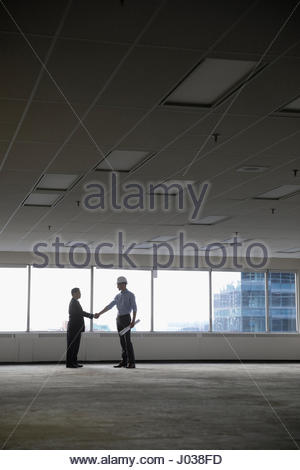 Contractor and businessman shaking hands in unfinished, empty urban open plan office - Stock Photo
