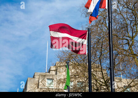 Latvian flag on a flagpole against blue sky - Stock Photo