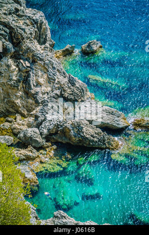 Tourists shorkling between Rocks in Azure Bay of Beautiful Paleokastritsa in Corfu Island, Greece - Stock Photo