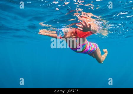 Happy baby girl in snorkeling mask dive underwater with fun in sea pool. Healthy lifestyle, people water sport outdoor - Stock Photo