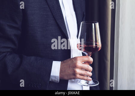 Horizontal close up of Caucasian man in black suit and white shirt holding a tall glass with rose wine  at an event - Stock Photo
