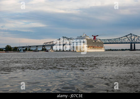 The cruise ship Carnival Dream passes under the Crescent City Connection bridge in New Orleans on its way down the - Stock Photo