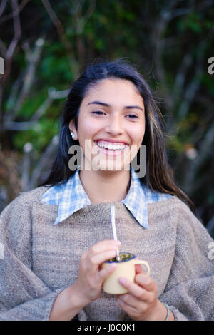 A Patagonian girl in a traditional wool poncho with a bombilla straw drinking yerba mate, Patagonia, Chile - Stock Photo