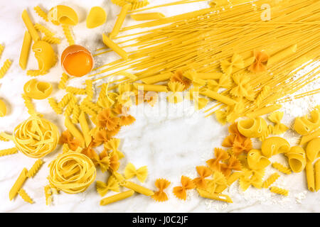 Various types of pasta with egg on marble with copyspace - Stock Photo