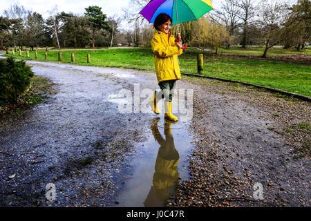 Boy in yellow anorak carrying umbrella in park - Stock Photo