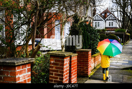 Rear view of boy in yellow anorak carrying umbrella along street - Stock Photo