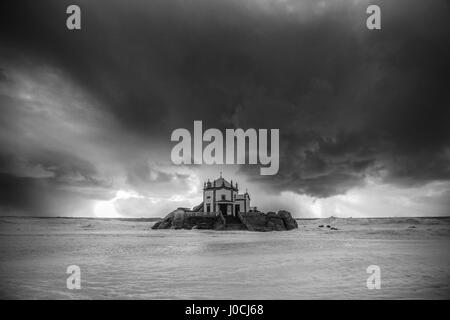 Photo of a church Senhor da Pedra in the beach of Miramar in Portugal. Dark storm clouds approaching to the shore, - Stock Photo