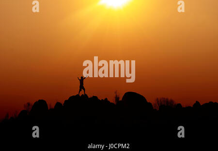 Silhouette of a man standing on top of a hill. Freedom and success concept. - Stock Photo