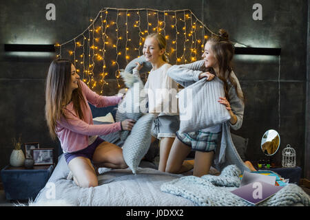 Three beautiful young women fighting with pillows on bed and laughing - Stock Photo