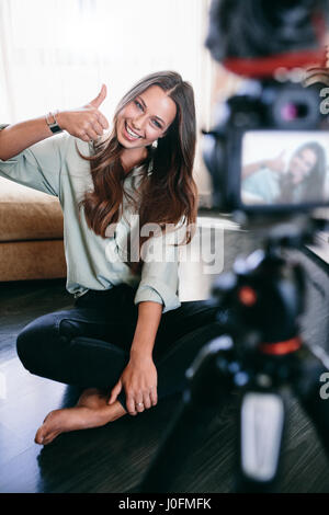 Young vlogger showing thumb up sign recording her videoblog. Smiling woman sitting on floor recording content on - Stock Photo