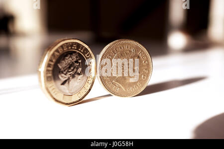 The new pound coin (left) and old pound coin British money sterling - Stock Photo