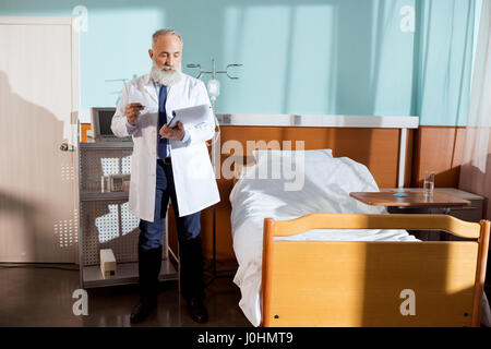Concentrated senior bearded male doctor making notes in clipboard - Stock Photo