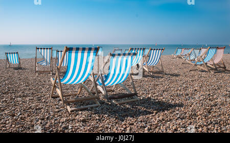 Empty traditional striped deckchairs on Brighton beach, England, UK - Stock Photo