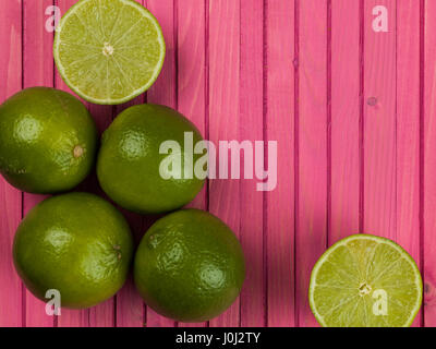 Fresh Ripe Juicy Limes Citrus Fruit Against a Pink Background - Stock Photo