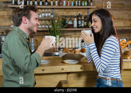 Couple interacting each other while having coffee at counter in café - Stock Photo