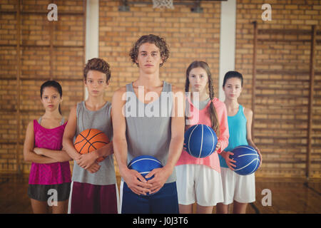 Portrait of confident high school kids holding basketball in the court - Stock Photo
