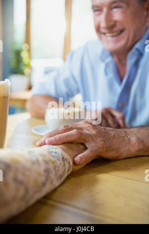 Senior couple holding hands while having coffee in café - Stock Photo
