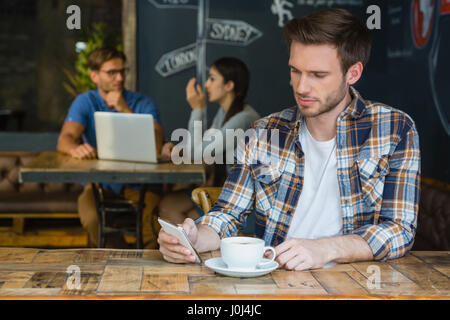 Man using mobile phone while having coffee in café - Stock Photo