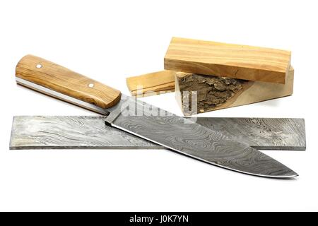handmade damascus kitchen knife with raw materials isolated on white background - Stock Photo