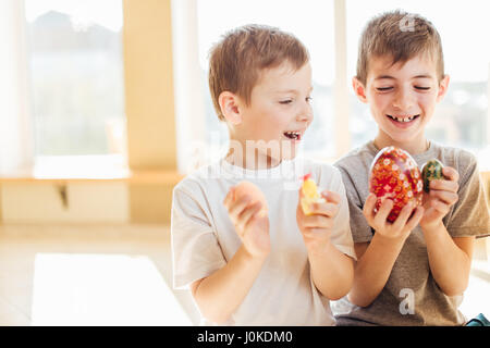 Two boys holding easter eggs and smile to each other - Stock Photo