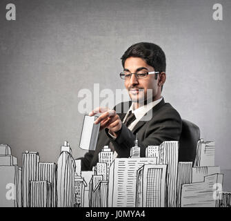 Businessman playing with drawn skyscrapers - Stock Photo