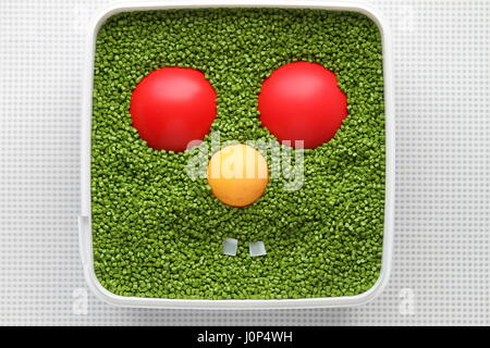 Green emoticon with red eyes, yellow nose on a white background. Emoticon for use in computer games and web design. - Stock Photo