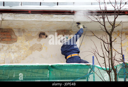 The worker in protective glasses and a respirator processes the wall with an angle grinder before restoration and - Stock Photo