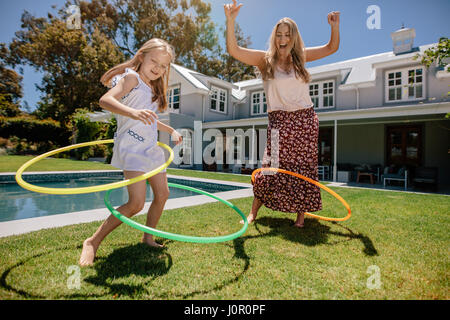 Woman and young girl outdoors using hula hoops and smiling. Mother and daughter playing with hula hoop in their - Stock Photo