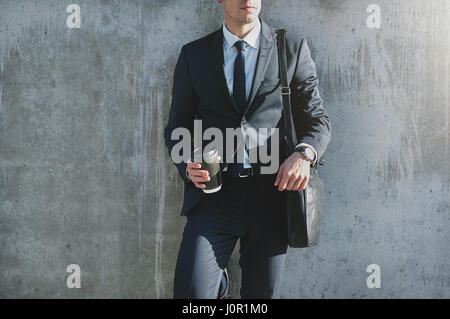Stylish contemporary businessman standing at the gray wall and holding a cup of coffee. - Stock Photo