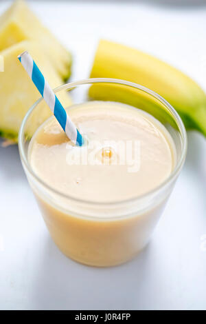 Pina colada pineapple banana smoothie with blue straw - Stock Photo