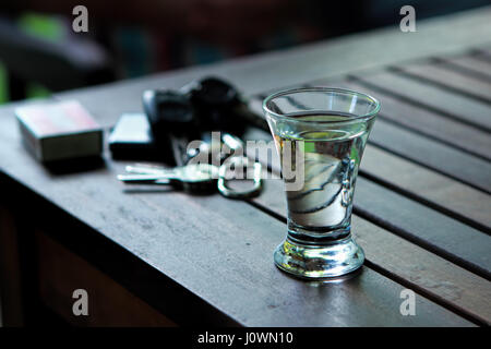 Vodka shot on table with matches and keys in the background - Stock Photo