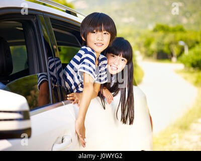 happy asian little boy and girl sticking their heads out of car window - Stock Photo
