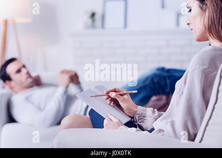 Confident professional psychologist taking notes - Stock Photo