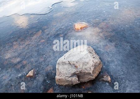 Stone lays on Saimaa lake coast covered with ice - Stock Photo