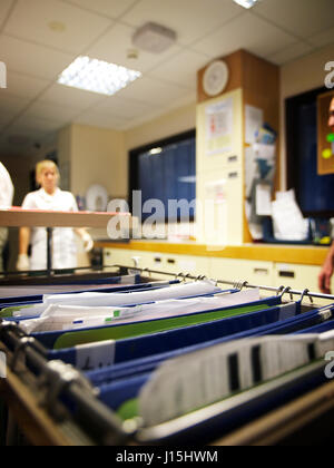 Patient notes with medical staff walking in background  on busy ward in large general hospital - Stock Photo