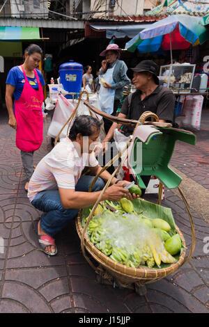 Street food vendor making mango salad in Chinatown, Bangkok, Thailand - Stock Photo