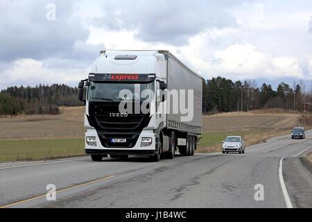 SALO, FINLAND - APRIL 13, 2017: White Iveco Stralis Hi-Way semi truck hauls curtainsider trailer among traffic on - Stock Photo